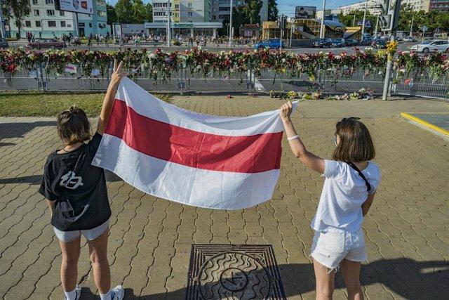 Dos personas con la bandera de Bielorrusia delante del memorial a uno de los fallecidos en las manifestaciones en Minsk