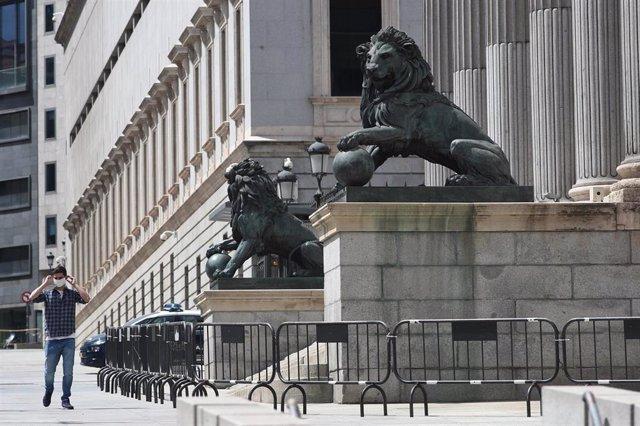 Un hombre se coloca una mascarilla mientras camina por delante de la fachada del Congreso de los Diputados