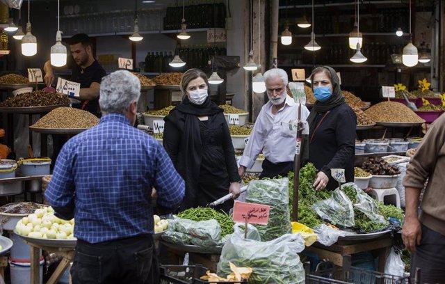 Personas con mascarilla enun mercado de Rasht, Irán