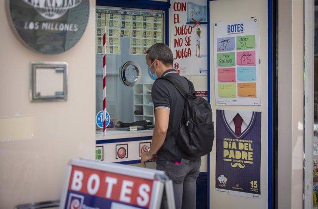 Un cliente compra lotería en una administración