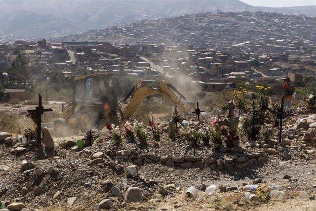 Una excavadora cava tumbas para personas que han muerto a causa de la COVID-19 en Cochabamba, Bolivia.