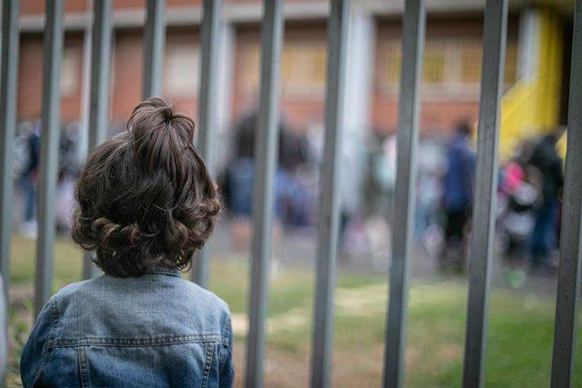 Un niño de espaldas a las puertas de un colegio