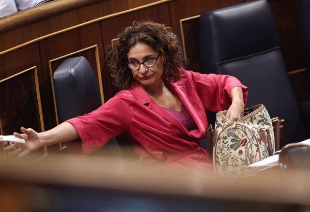 La ministra d'Hisenda, María Jesús Montero, cerca en la seva bossa una mascarilla i un diputat li presta una altra  al Congrés durant la sessió plenària.