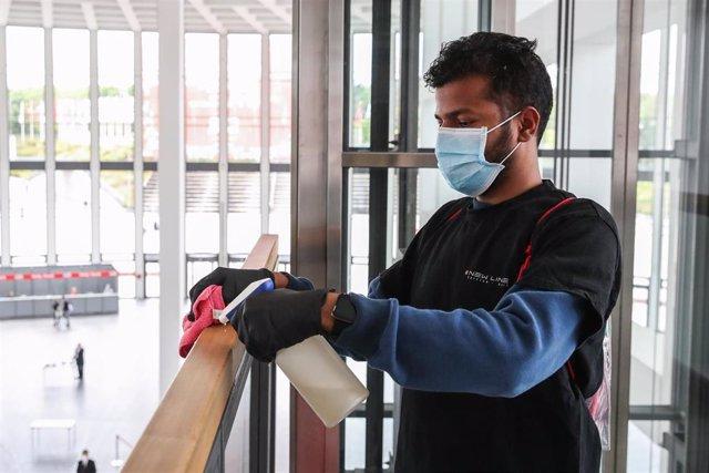 Un trabajador desinfectando una barandilla en la feria IFA en Berlín