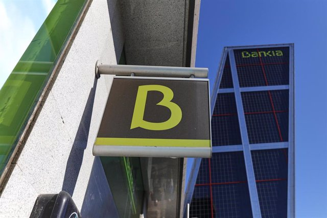 Oficina de Bankia y su sede en la torre Kio de Madrid.