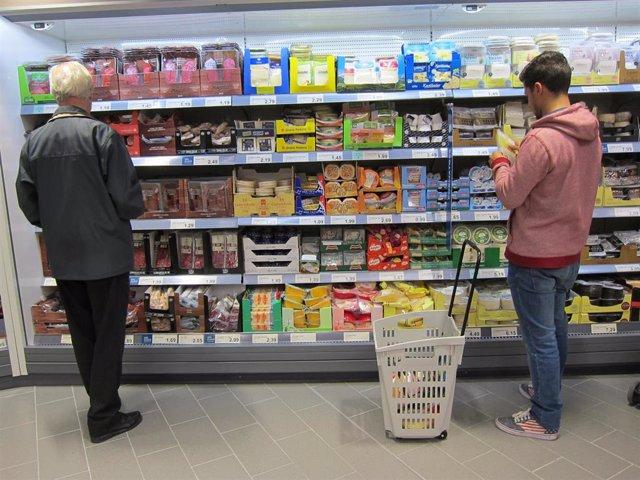 Dos personas compran en un supermercado.