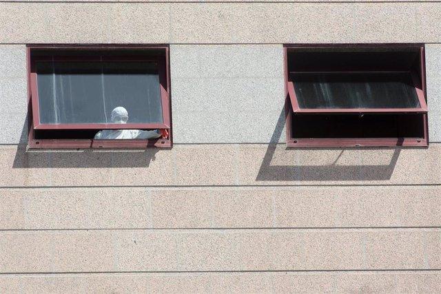 Un trabajador protegido es visto por uno de los cristales de la residencia de mayores DomusVi de Outeiro de Rei en Lugo, Galicia (España), a 8 de septiembre de 2020. La Xunta ha intervenido el geriátrico tras detectar 99 positivos más en covid-19, 94 de e