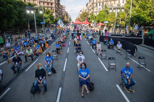 Participants asseguts en les cadires de separació l'acte de l'ANC, Òmnium i l'AMI per la Diada a la plaça Letamendi de Barcelona