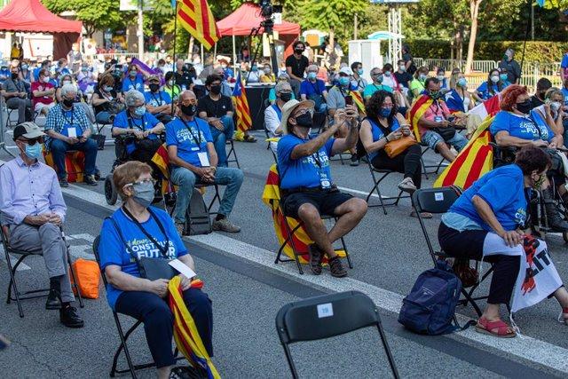 Participants asseguts en les cadires de separació en una concentració de l'ANC, Òmnium i l'AMI per la Diada, a la plaça Letamendi de Barcelona