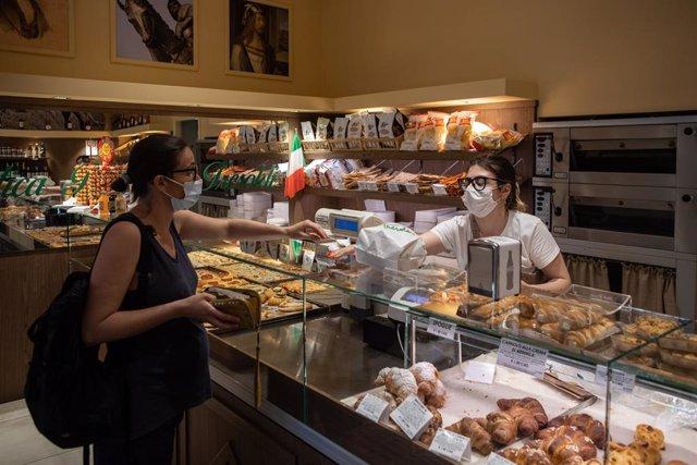 Mujeres con mascarilla en una panadería de Bérgamo, Italia