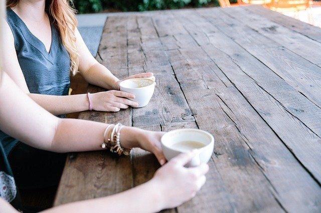 Dos mujeres charlando mientas toman un café.