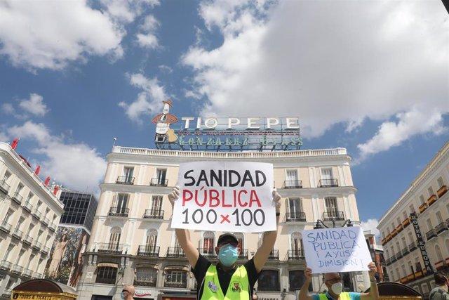 """Un miembro del Movimiento Pensionista de Madrid sostiene un cartel en el que se lee 'Sanidad Pública 100 x 100' durante la concentración frente a la Real Casa de Correos en defensa de la sanidad pública, de las residencias públicas y las pensiones """"dignas"""