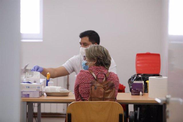 Un sanitario de Cruz Roja realiza a una mujer un test rápido de detección de anticuerpos IgG e IgM utilizado en el Instituto de Formación Integral en Seguridad y Emergencias (IFISE), en Colmenar Viejo, Madrid (España).