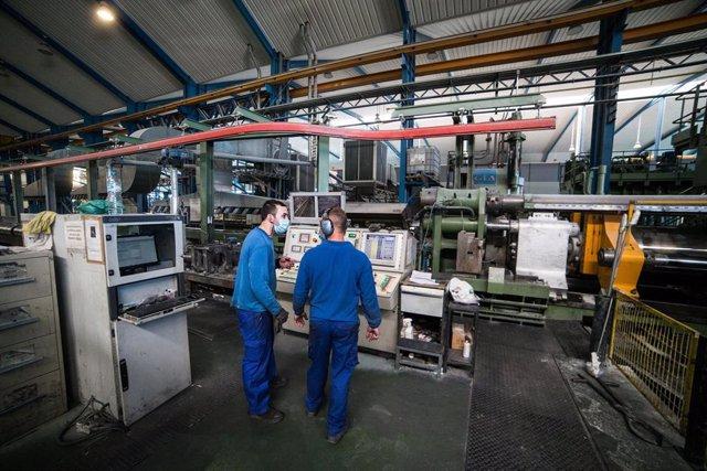 Varios trabajadores durante su jornada laboral en la empresa Extrusión Toledo, innovadora en la fabricación de perfiles metálicos, que ha creado y patentado un modelo de separadores en restaurantes durante la pandemia de Covid-19, en Toledo, Castilla-La M