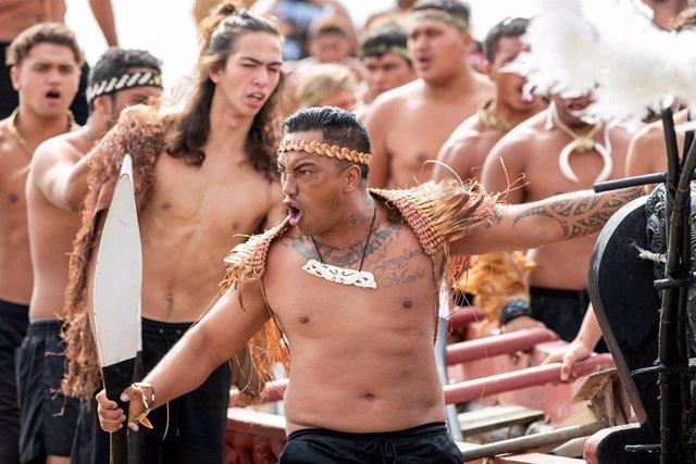 Varios maoríes interpretando una haka en la playa de Te Tii