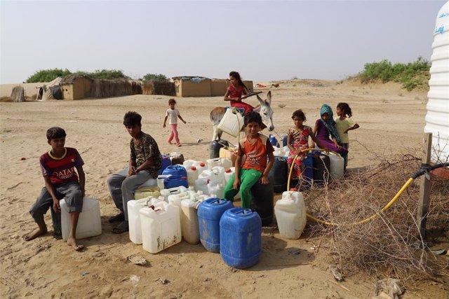 Niños esperan para llenar bidones de agua en Yemen