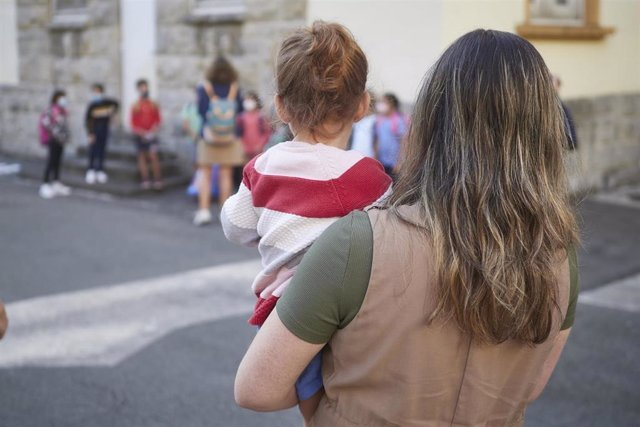 Una madre carga con su hija en el patio del Colegio Público Víctor Pradera en el primer día de colegio del curso escolar 2020-2021 en Pamplona