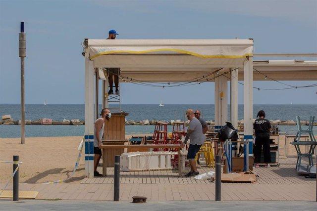 Varios trabajadores preparan la terraza de un bar junto a la playa durante el segundo día de la reapertura al público de las terrazas al aire libre de los establecimientos de hostelería y restauración limitándose al 50% de las mesas y garantizándose una d