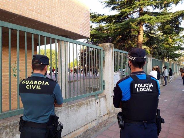 Agentes de Policía Nacional revisan el cumplimiento de las normas y que el regreso de los alumnos a la enseñanza presencial se haga de forma ordenada y segura a la puerta del I.E.S. Emilio Ferrari de Valladolid.