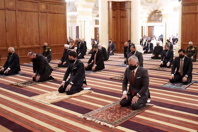 El rey Abdalá de Jordania y el príncipe heredero, Hussein bin Abdulá II, (segundo por la derecha) durante un rezo en una mezquita de Amán en medio de la pandemia de coronavirus