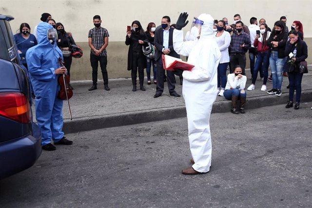 Un cura con traje protector habla durante un funeral celebrado por una víctima de la COVID-19 en Bogotá, Colombia.