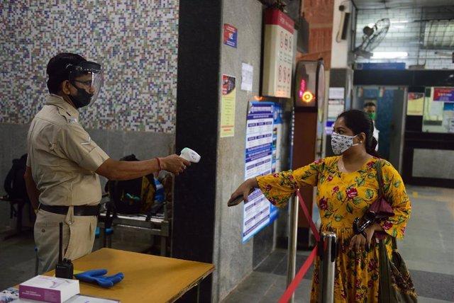 Un agente de la Policía de India toma la temperatura a una usuaria del metro de Calcuta antes de acceda a uno de los trenes.