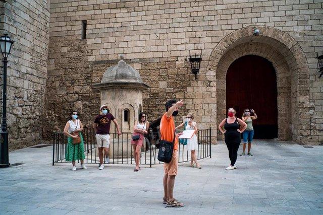 Varios turistas junto al Palacio de la Almudaina de Palma.