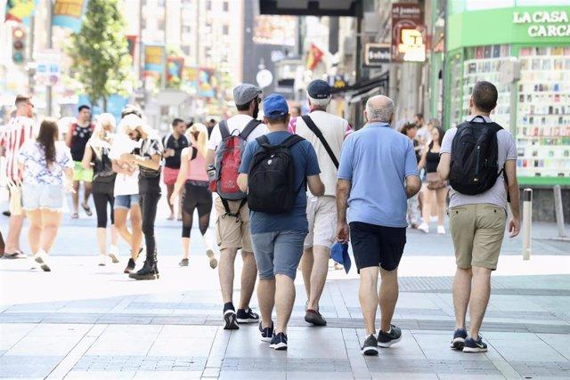 Un grupo de hombres caminan por una calle de Madrid.