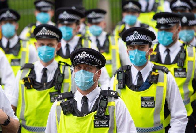 Policías con mascarilla en Londres desplegados ante una protesta del movimiento Extinction Rebellion