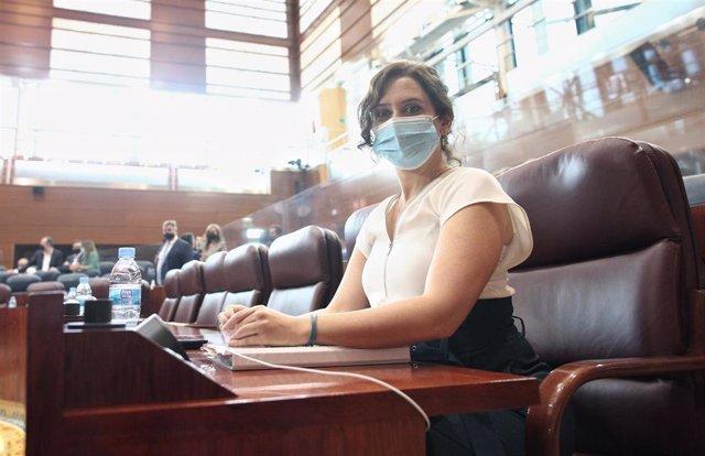 La presidenta de la Comunidad de Madrid, Isabel Díaz Ayuso, sentada en su escaño de la Asamblea de Madrid