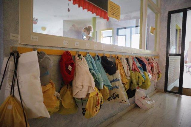 Chaquetas de los alumnos colgadas en la pared de una Escuela Infantil , foto de archivo