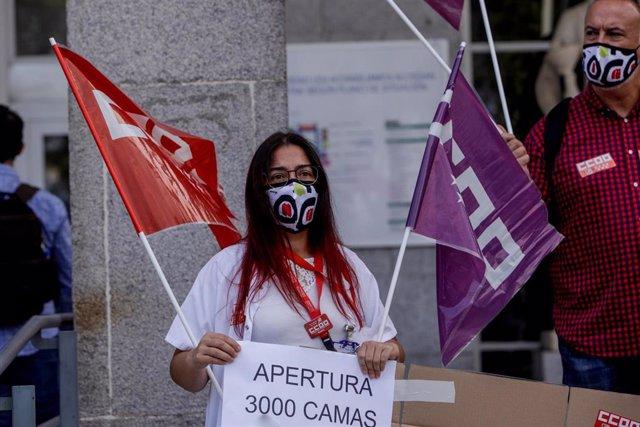 """Una trabajadora sanitaria sostiene una pancarta donde se puede leer """"Apertura 3000 camas"""" en una concentración frente al Hospital Clínico San Carlos, en Madrid (España), a 15 de septiembre de 2020."""