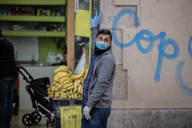 Un home protegit amb mascarilla i guants en la porta del seu establiment d'alimentació al barri del Raval (Arxiu)
