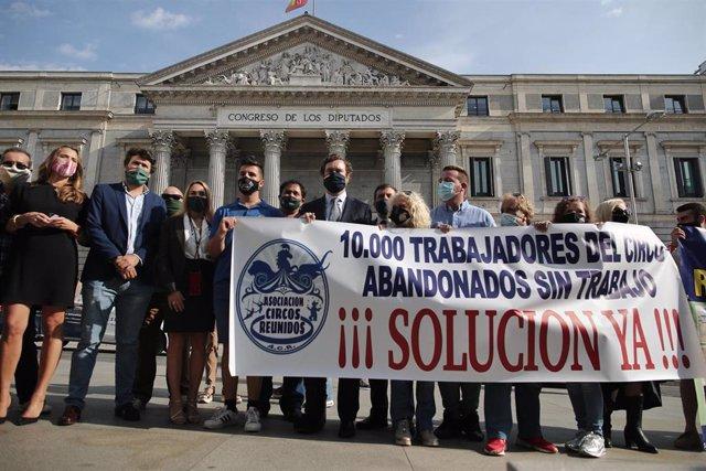 Componentes de la asociación Circos Reunidos sostienen una pancarta como signo de protesta durante una manifestación convocada frente al Congreso, junto a varios diputados de Vox