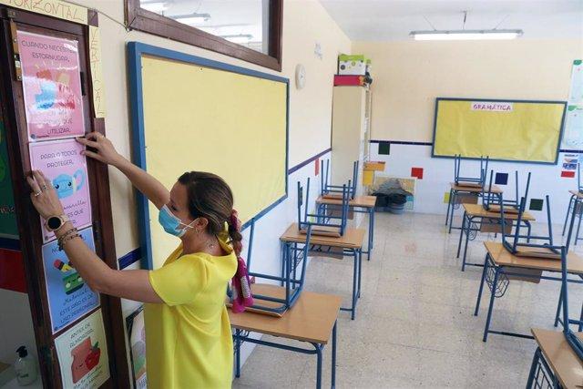 Una profesora coloca carteles de medidas preventivas ante el COVID-19 en el aula antes del inicio del curso escolar en el del colegio público Pablo Neruda.. Málaga a 9 de septiembre 2020