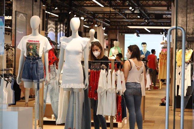 Personas con mascarilla en el interior de una tienda de ropa en el primer día de la fase 1 en Madrid, en la que se permite reapertura de locales y establecimientos minoristas con una superficie igual o inferior a 400 metros cuadrados. En Madrid (España),