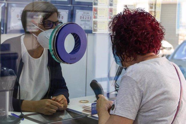 Una lotera de una administración atiende a una clienta