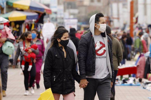 Una pareja camina por uno de los mercadillos urbanos de Lima, la capital peruana.