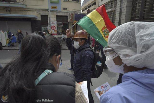 Una cooperativa minera protesta en las calles de La Paz, cerca de otra movilización convocada por los profesionales sanitarios en protesta de las condiciones laborales a las que tienen que hacer frente en plena crisis del coronavirus.
