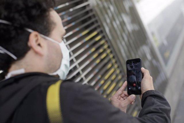 Un hombre protegido con mascarilla realiza una videollamada por su teléfono móvil en Madrid en abril de 2020