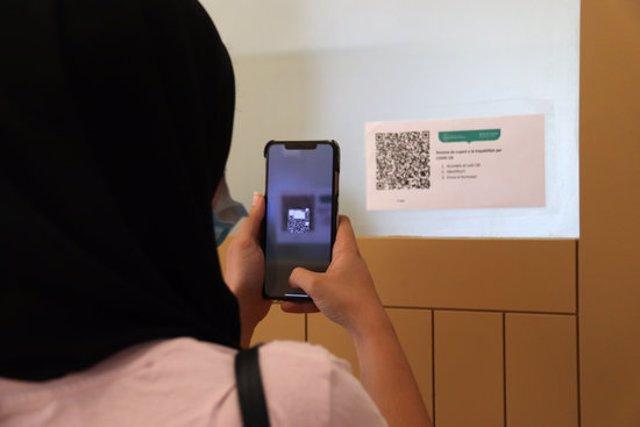 Pla obert d'una alumna capturant un codi QR amb el mòbil per registrar la seva assistència a l'aula a la Facultat de Ciències Econòmiques i Empresarials el 14 de setembre de 2020 (Horitzontal)
