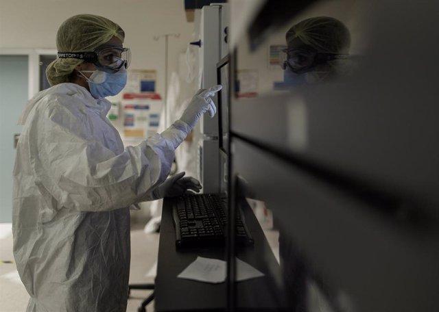 Un trabajador sanitario en la puerta de la habitación de un paciente ingresado en una Unidad de Cuidados Intensivos, foto de archivo