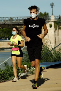 Varios adultos hacen ejercicio junto al río Segura