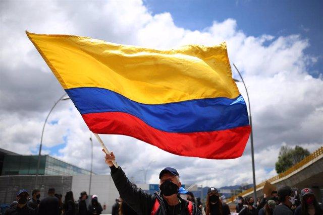 Un hombre con mascarilla ondea una bandera de Colombia.