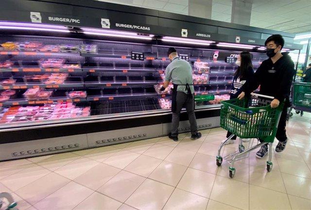 Una pareja protegidos con mascarilla realizan la compra en un supermercado.