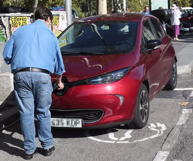 Un hombre carga su coche en un punto de carga para coches eléctricos en Madrid.