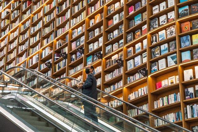 Un hombre con mascarilla en una biblioteca de Seúl
