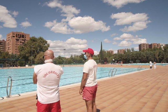 Dos socorristas vigilan la piscina del Polideportivo Vicente del Bosque en Madrid  antes de su cierre por adelantado el 1 de septiembre junto al resto de piscinas municipales de la ciudad, una medida para evitar más propagaciones del coronavirus ante los