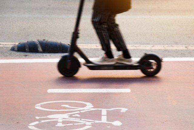 Pla tancat d'un patinet elèctric circulant en un carril bici amb el símbol d'una bici dibuixat al costat el 18 de setembre de 2020 (Horitzontal)