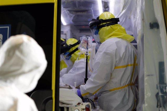 Sanitarios del SUMMA protegidos con un traje protector frente al Covid-19 trasladan a un paciente desde la UVI de IFEMA al interior de la unidad móvil para su posterior traslado al Hospital Puerta de Hierro, durante un día de trabajo del Servicio de Urgen